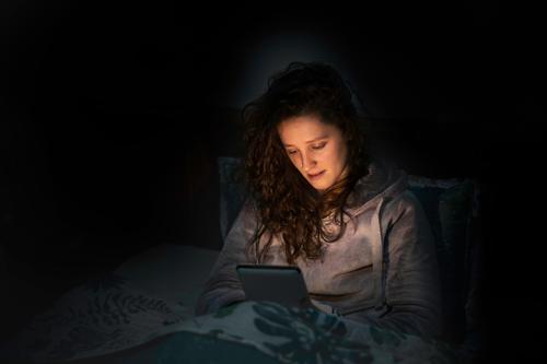 Mädchen, das vor dem Schlafengehen im Bett ihre Tablette oder ihr E-Book liest im Innenbereich ruhen Frau Schlafenszeit Abend Freizeit Browsen Lügen Zeit