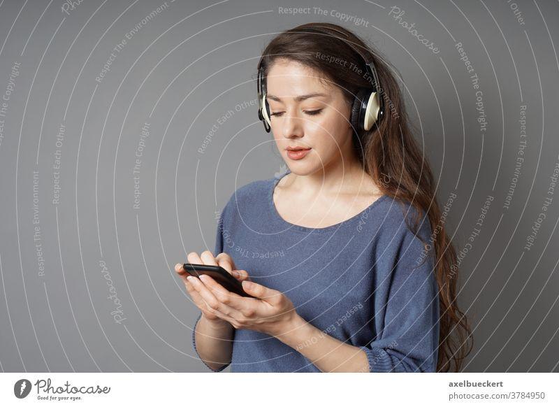 junge Frau, die mit kabellosen Kopfhörern und einem Smartphone Musik hört Bluetooth Mobile Drahtlos Schnurlos Zelle Telefon klug zuhören Mädchen Person Menschen