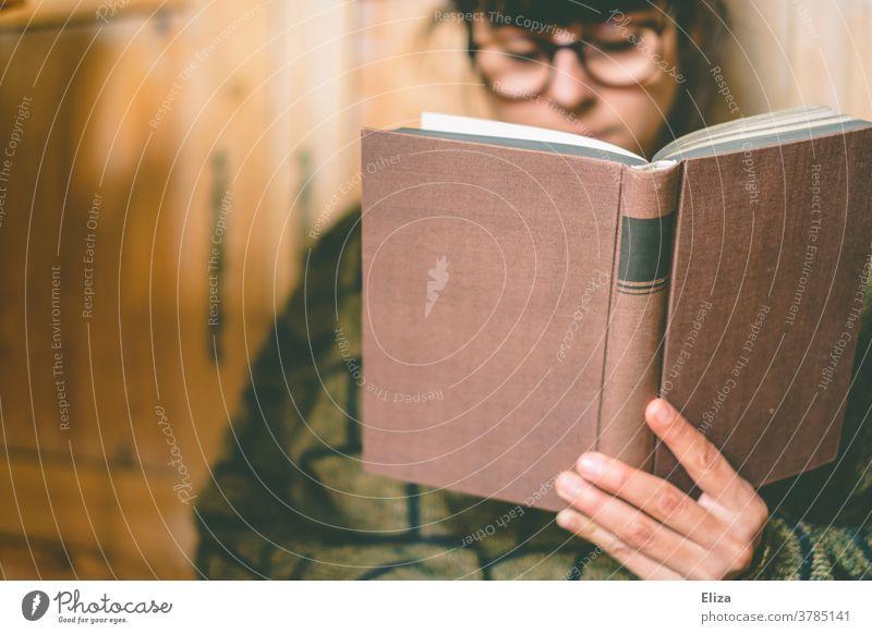 Eine frau mit Brille liest zuhause ein Buch lesen Leseratte gemütlich Lesestoff Roman Bildung Literatur vertieft konzentriert Pullover dunkelhaarig brünett