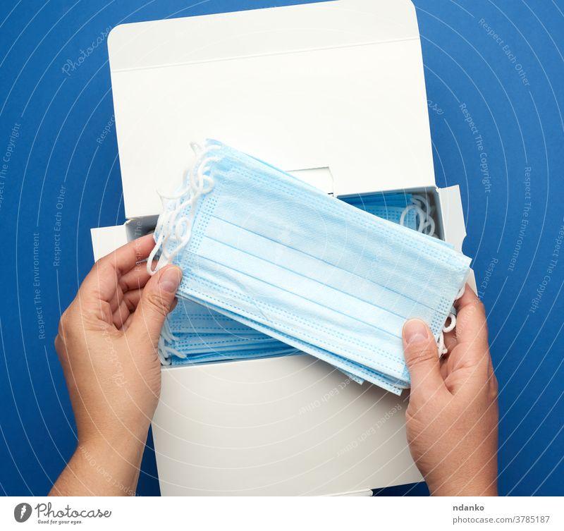 Schachtel mit medizinischen Einwegmasken und zwei Frauenhänden, blauer Hintergrund Hand Halt Kasten Mundschutz Medizin Pandemie Lungenentzündung Prävention