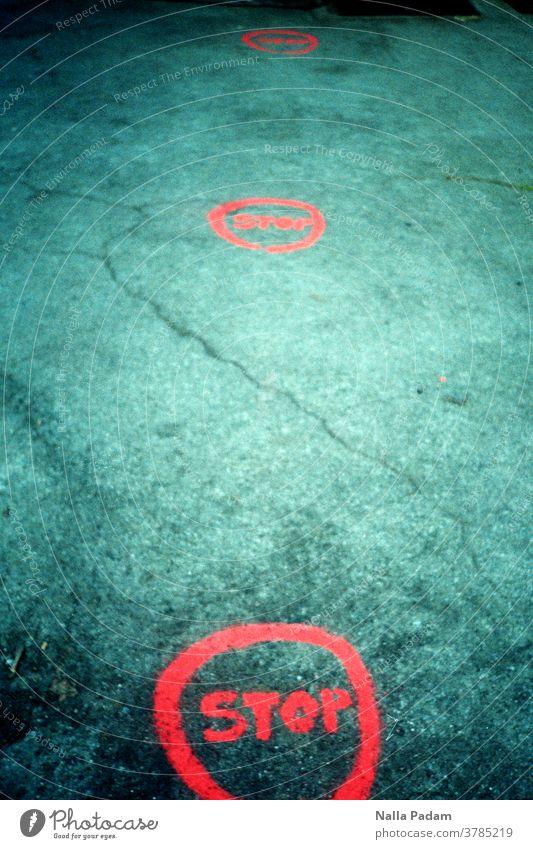 Stop im Kreis auf Beton Prävention Abstandsregel COVID Schutz Pandemie Coronavirus Virus Stadt Bürgersteig Tag Straße Außenaufnahme Orange Farbfoto Hygiene