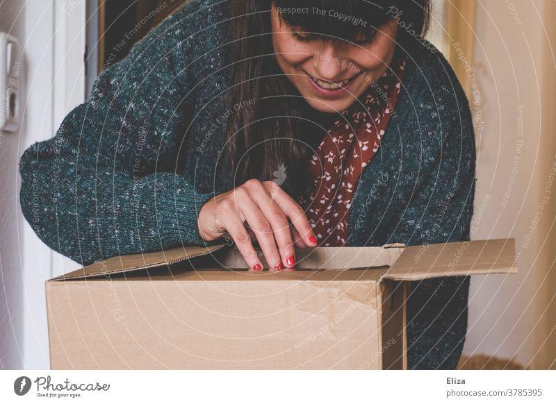 Eine junge Frau öffnet neugierig und voller Vorfreude ein Paket Onlineshopping auspacken Freude online bestellen Post Geschenk Überraschung lächeln Verpackung