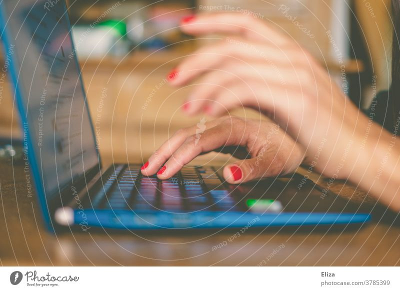 Die Hände einer Frau tippen etwas auf dem Notebook. Home Office. Tastatur Business online schreiben arbeiten weiblich Internet blau zuhause Tisch