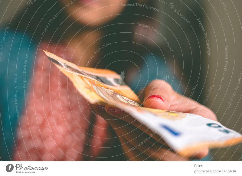 Eine Frau gibt einen 50 Euro Schein Taschengeld bezahlen Schwarzarbeit überreichen schenken Geld Bargeld kaufen Investition Finanzen Konsum