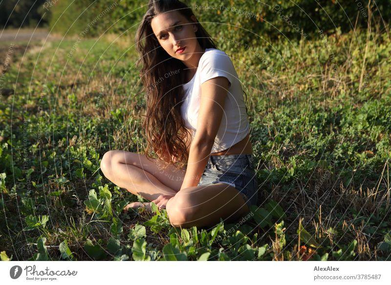 Portrait einer jungen Frau, die am Feldrand vor einem Wald sitzt schön nah fit anmutig Haut Gesicht schauen direkt langhaarig schlank sportlich 18-30 Jahre