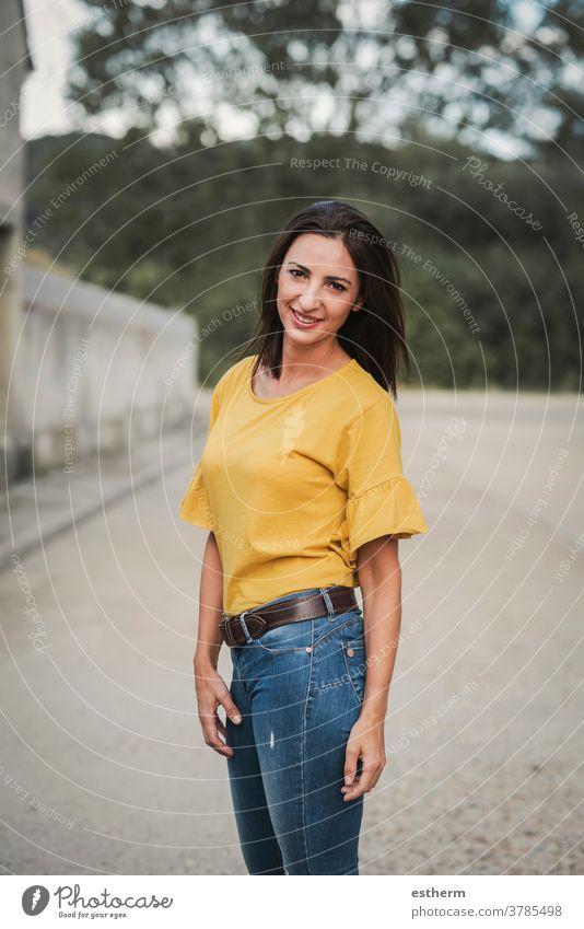 Lächelnde junge Frau, die auf der Straße steht Junge Frau schön elegant Stehen urban gefühlsbetont gestikulierend natürlich lässig Ausdruck Menschen Mode
