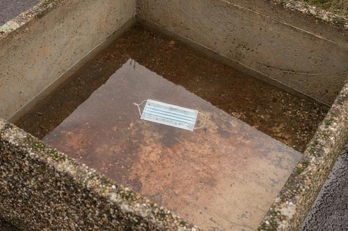 Coronakrise Mundschutz schwimmt in großem Blumenkübel, der teilweise mit Regenwasser gefüllt ist coronakrise Müll weggeworfen schwimmen Wasser quadratisch
