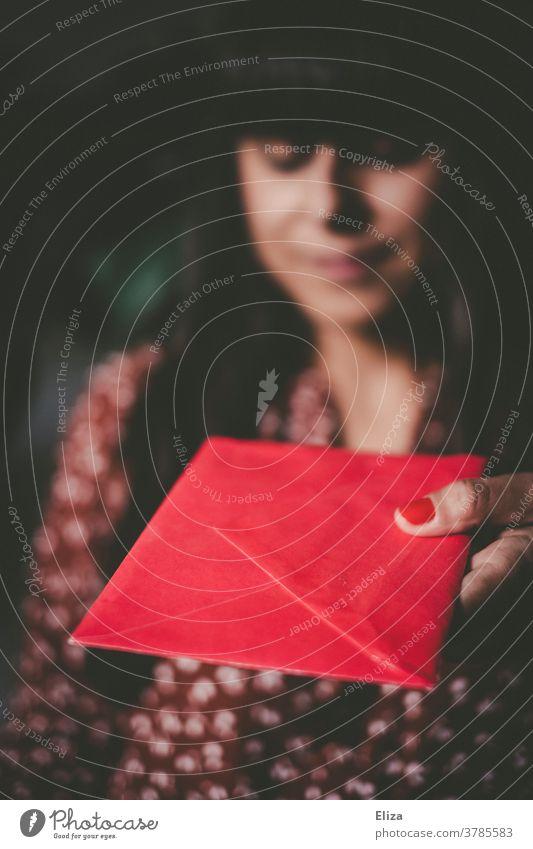 Eine Frau überreicht einen roten Briefumschlag. Liebesbrief. Brief. Geschenk. Umschlag geben überreichen Post Gutschein Valentinstag schenken Glückwunschkarte