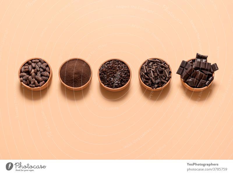 Kakao- und Schokoladenzutaten in Schalen. Kakaobohnen und Schokoladenmischung in der Draufsicht obere Ansicht ausgerichtet Sortiment Hintergrund backen beige