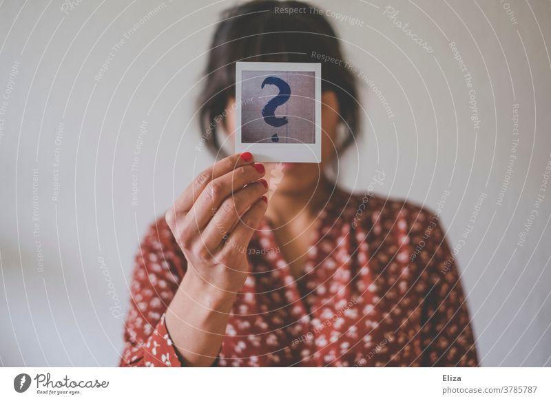Identitätskrise. Junge Frau hält ein Polaroid mit einem großen Fragezeichen vor ihr Gesicht. Mensch ratlose unsicher Unsicherheit Gefühle Hintergrund neutral