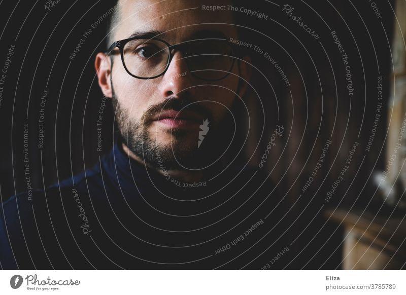 Portrait eines dunkelhaarigen Mannes mit Brille und Bart. Ernster Blick in die Kamera. ernst Mensch Porträt Erwachsene Gesicht Innenaufnahme Halbschatten düster