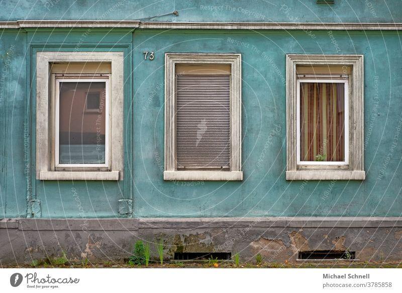 Triste Hauswand eines alten Hauses mit drei Fenstern, eines davon mit geschlossenen Rolladen Wand Fassade Mauer Menschenleer Außenaufnahme Farbfoto Gebäude Tag