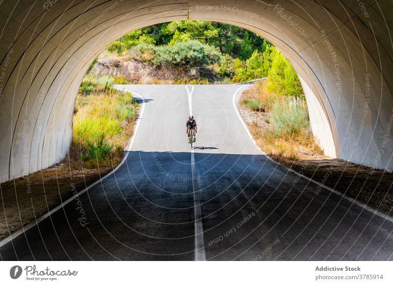 Radfahrer fahren Fahrrad unter Brücke in der Landschaft Mitfahrgelegenheit Straße Mann Bogen aktiv Lifestyle Sport Aktivität Gesundheit Sommer Viadukt Torbogen