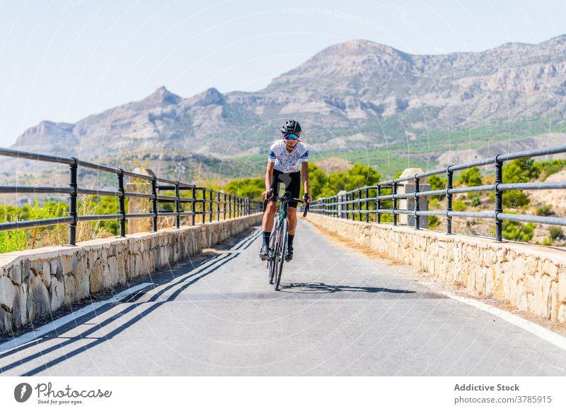 Radfahrer auf der Landstraße im Hochland Fahrrad Mitfahrgelegenheit Straße Berge u. Gebirge aktiv Sport Route Training Natur Frau Lifestyle Aktivität Gesundheit