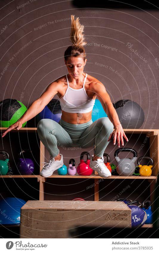 Starke Frau springt auf Box im Fitnessstudio springen Kasten Sport stark Bestimmen Sie passen operativ Training hölzern Sportlerin Übung Athlet Gesundheit