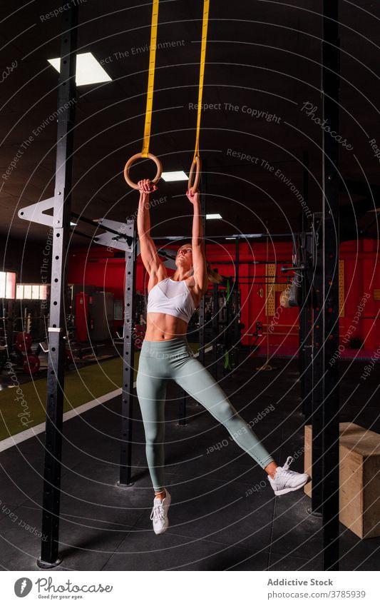 Ausdauersportlerin bei Übungen an Gymnastikringen gymnastisch Ring Training Bauchmuskeln Frau Gleichgewicht stark anstrengen Unterleib calisthenics Fitness