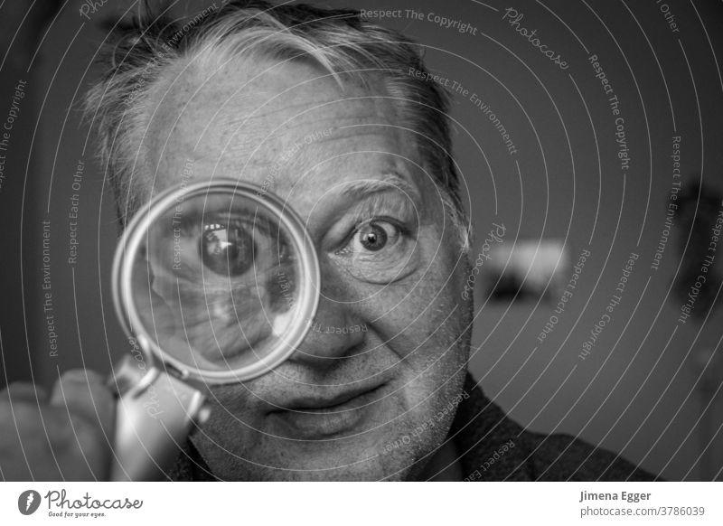 älterer Mann schaut durch Lupe vergrößert Auge Blick Linse Glas untersuchen Suche Mensch Detektiv Neugier beobachten Porträt Blick in die Kamera Gesicht