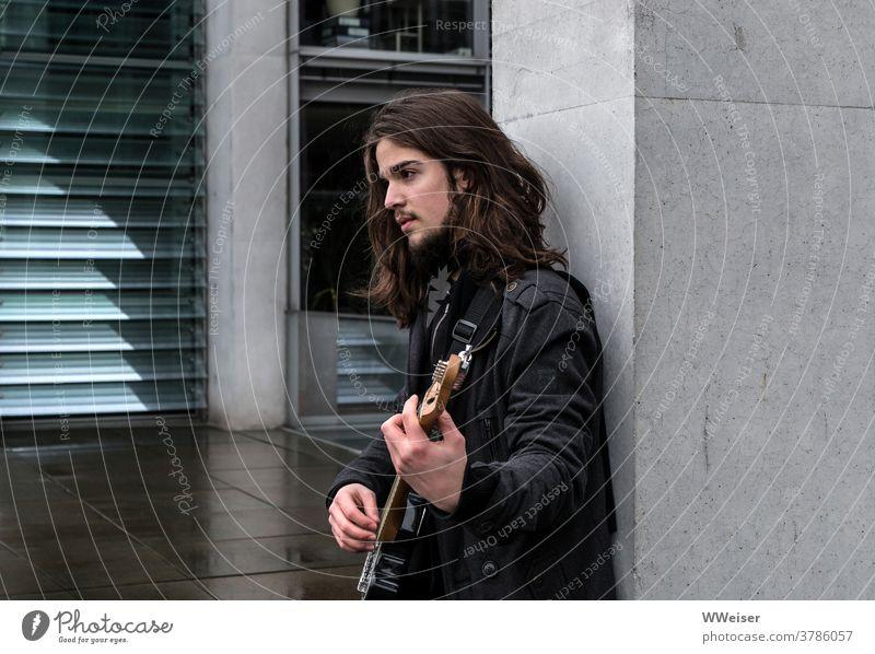 Ein junger Musiker singt im Regierungsviertel Berlin und zupft auf seiner Gitarre Bassgitarre Lied Straßenmusik nachdenklich traurig melancholisch Haare Gebäude