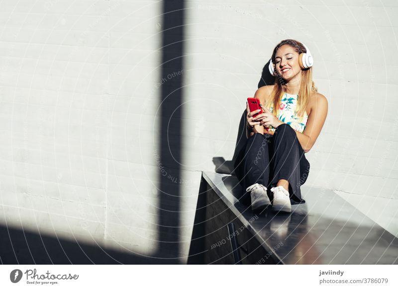 Mädchen mit einem Smartphone in Freizeitkleidung Frau Kopfhörer klug Telefon Teenager Generation Kaukasier gen z jung Person Lifestyle Mobile Funktelefon