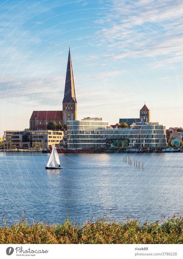 Blick auf die Hansestadt Rostock mit Petrikirche, Nikolaikirche und Silohalbinsel Segelboot Warnow Fluss Stadthafen Mecklenburg-Vorpommern Tourismus Schiff Boot