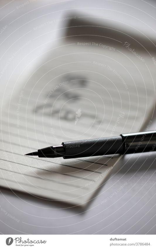 Schwarzer Stift liegt auf liniertem Zettel Notiz Papier schreiben Schreibwaren Schreibstift Innenaufnahme Bildung Arbeitsplatz Schule Büro Büroarbeit Studium