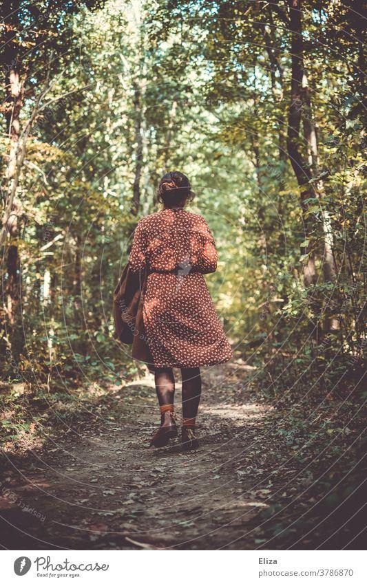 Frau in einem rotweiß gemusterten Kleid geht im Herbst im Wald spazieren. Spaziergang gehen Rückansicht Waldspaziergang Natur alleine Weg Ruhe grün Bäume
