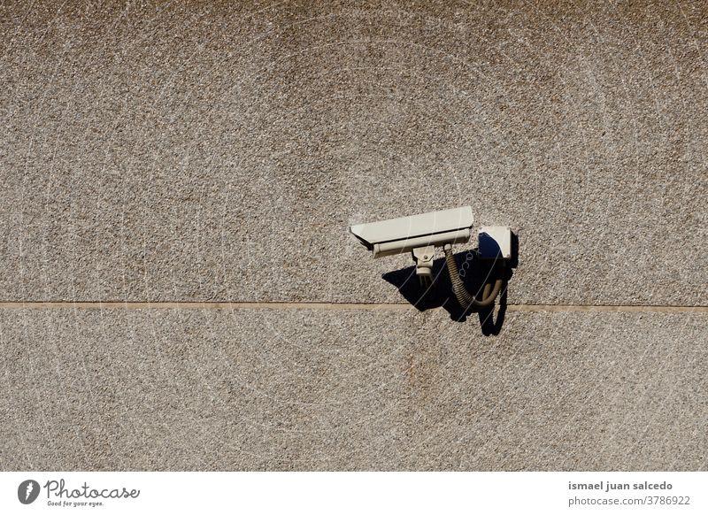 Sicherheitskamera an der Gebäudewand Fotokamera Videokamera Überwachungskamera Wand Hintergrund Straße Gerät Schutz Technik & Technologie System Kontrolle