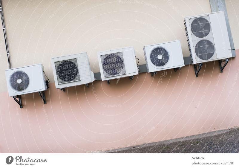 Klimakonferenz hängt schief, mehrere Wärmetauscher energieverschlingender Klimaanlagen an einer rosa Wand montiert symbolisch Energieverschwendung Hitzewelle