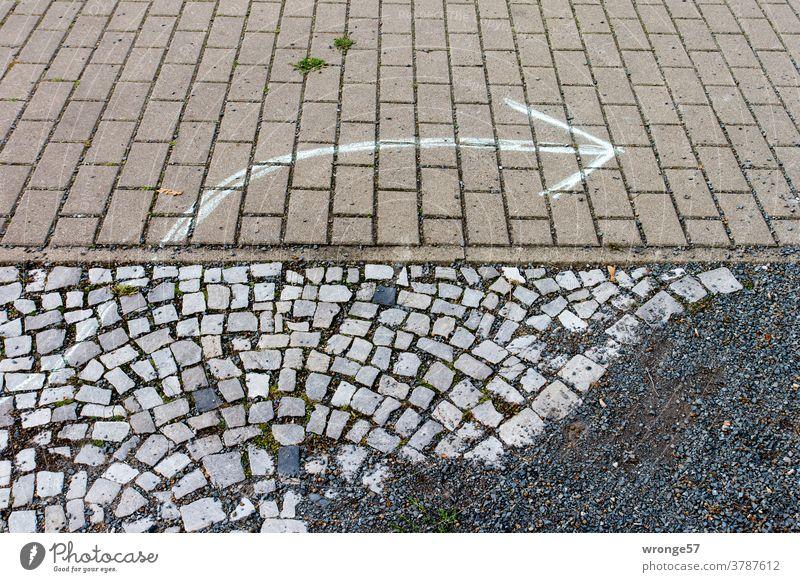 Empfehlung | ein mit weißer Kreide auf das Steinpflaster gezeichneter Pfeil gibt die Richtung nach rechts vor richtungsweisend Pfeilsymbol Kreidezeichnung