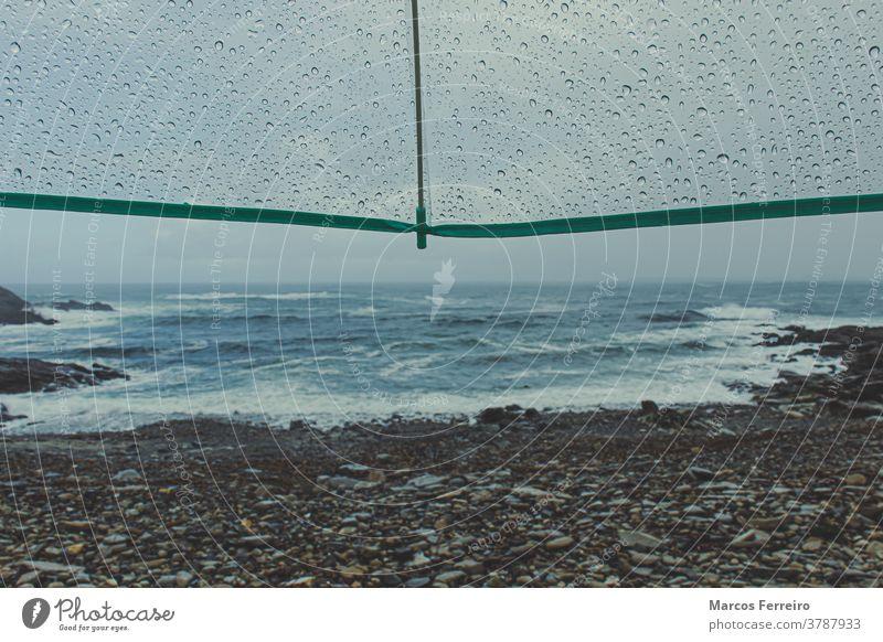 Blick auf die Küste mit Regenschirm mit Regentropfen Wassertropfen Szene niemand allein Ufer dramatisch Tropfen Schutz Wellen Küstenlinie natürlich Gewitter