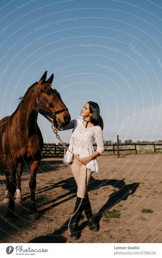 Lateinamerikanische Frau berührt den Kopf eines braunen Pferdes lateinamerikanisch streichelnd Freie Luft Feld Gras grün Himmel blau Bäume vertikal Patagonien