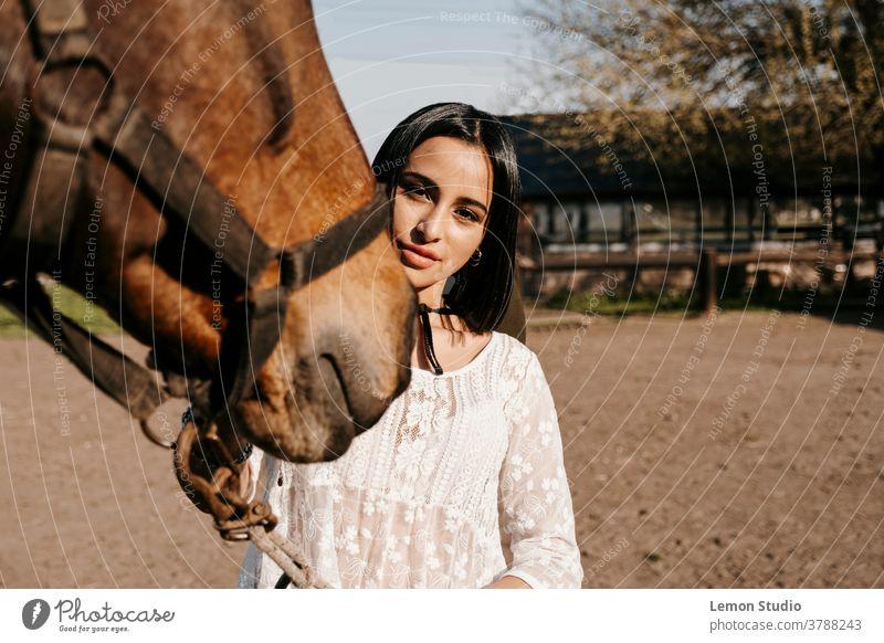 Nahaufnahme-Porträt einer Latina-Frau, die ein Pferd berührt Tier braun lateinamerikanisch Team Lächeln aktiv Dame Reiter Reiterin Eleganz Anzug Rennen