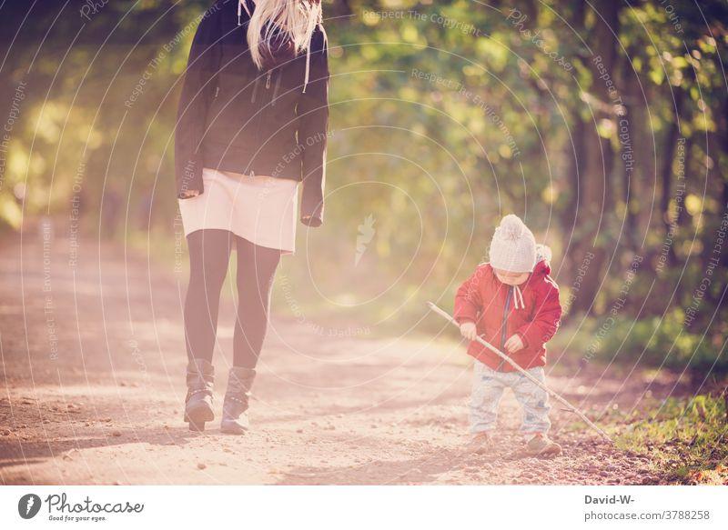 Mutter und Kind machen einen herbstlichen Spaziergang Familie Mama Sohn Wald zusammen Liebe gemeinsam spielen Stock Eltern Kleinkind