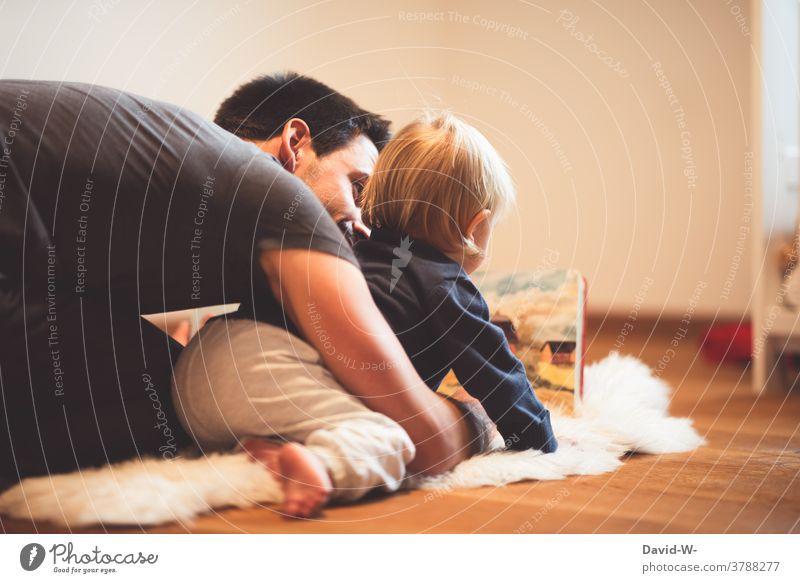 Vater und Sohn lesen zusammen ein Buch Kind anschauen gemeinsam Liebe nähe Freude Kindheit Zusammensein