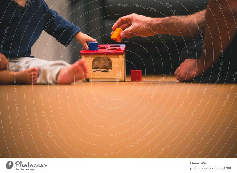 Vater und Kind spielen gemeinsam mit Bauklötzen und fördern die Motorik Entwicklung Spielzeug zusammen Liebe nähe Zusammensein Hände spaß Eltern Papa Sohn