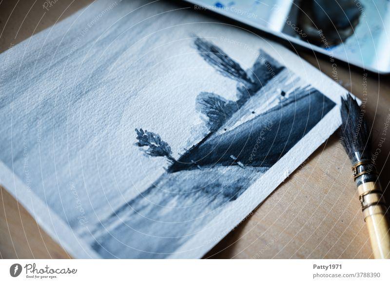 Kleines Aquarellbild einer ruhigen Landschaft mit Landstraße und Bäumen am Horizont. Ein Aquarellpinsel liegt daneben. Pinsel Kunst Hobby Malerei Kreativität