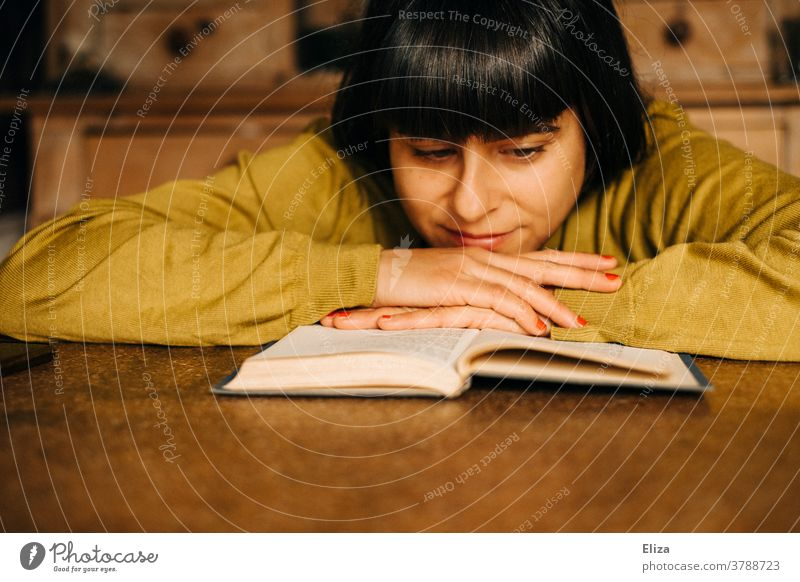 Eine Frau sitzt zuhause am Küchentisch und liest ein Buch lesen Leseratte gemütlich Lesestoff Roman Bildung Literatur vertieft konzentriert Pullover