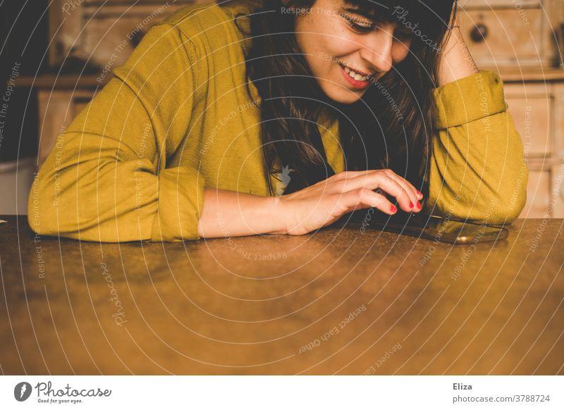 Junge Frau sitzt am Tisch und lächelt, während sie ihr Smartphone benutzt benutzen lächeln texten Freude Handy Lifestyle Telefon zuhause online lesen