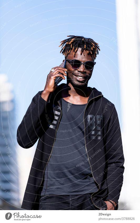 Schwarzer lächelnder Mann mit Sonnenbrille, der im Freien ein Mobiltelefon benutzt Afrikanisch schwarz Lächeln Menschen männlich Erwachsener Handy Typ Lifestyle