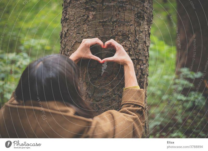 Eine Hand formt ein Herz am Stamm eines Baumes im Wald. Naturschutz. Naturverbundenheit Umweltschutz Liebe Baumstamm Frau Öko Klimaschutz Forstwirtschaft