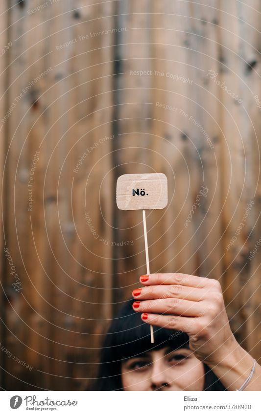 Eine Frau hält ein Schild mit der Aufschrift Nö hoch. Ablehnung, nein sagen, Trotz. Nein Protest Kommunizieren Absage nein heißt nein Weigerung Schriftzeichen