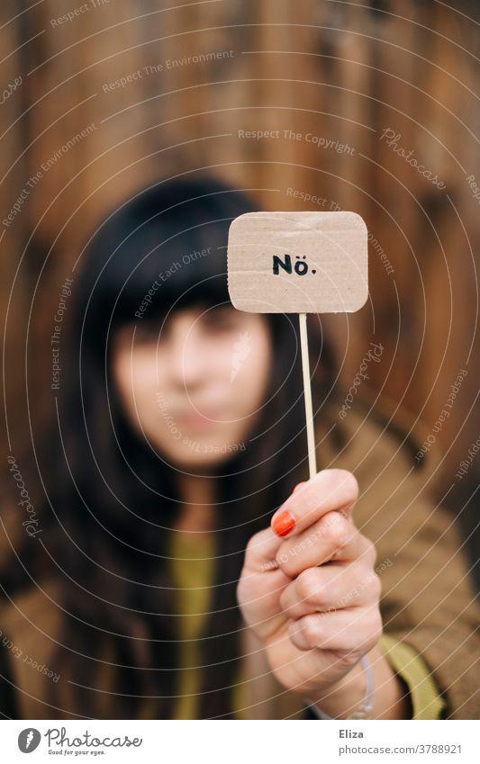 Eine dunkelhaarige Frau hält ein Schild mit der Aufschrift Nö hoch. Ablehnung, nein sagen, Trotz. Nein Protest Kommunizieren Absage nein heißt nein Weigerung