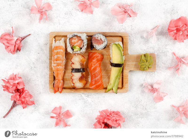 Sushi-Set Nigiri und Sushi-Rollen auf Holzbrett verzehrfertig Essen Sashimi Blumen Pastell Brötchen maki Sushi-Bar Esszimmer Meeresfrüchte Teller Holzplatte