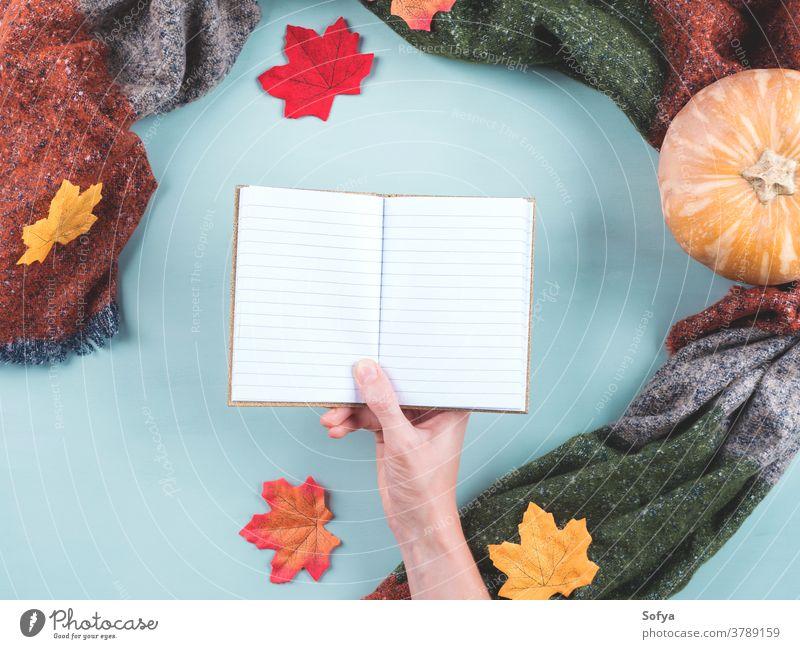 Leeres Notizbuch in Frauenhand im Schalrahmen fallen Herbst Hand Beteiligung Tagebuch blanko leer Page Planer Notebook Notizblock offen schreiben Journal Kürbis