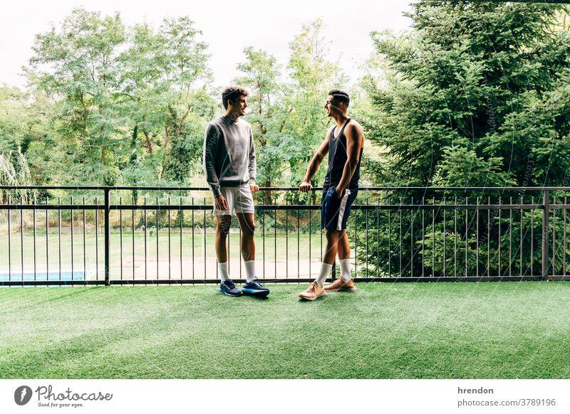 zwei in Sportkleidung gekleidete Männer unterhalten sich nach dem Training in der Turnhalle Menschen trainiert. Zwei Personen junger Erwachsener