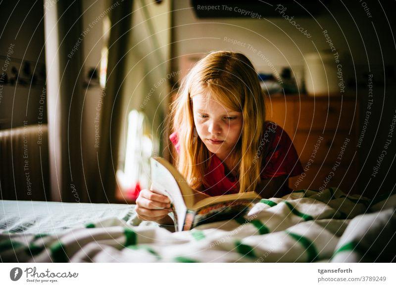 Kind liest Comics Kindheit lesen Lesen eines Buches Porträt Farbfoto Bildung Mädchen Innenaufnahme Konzentration Mensch lernen Wissen Literatur glücklich