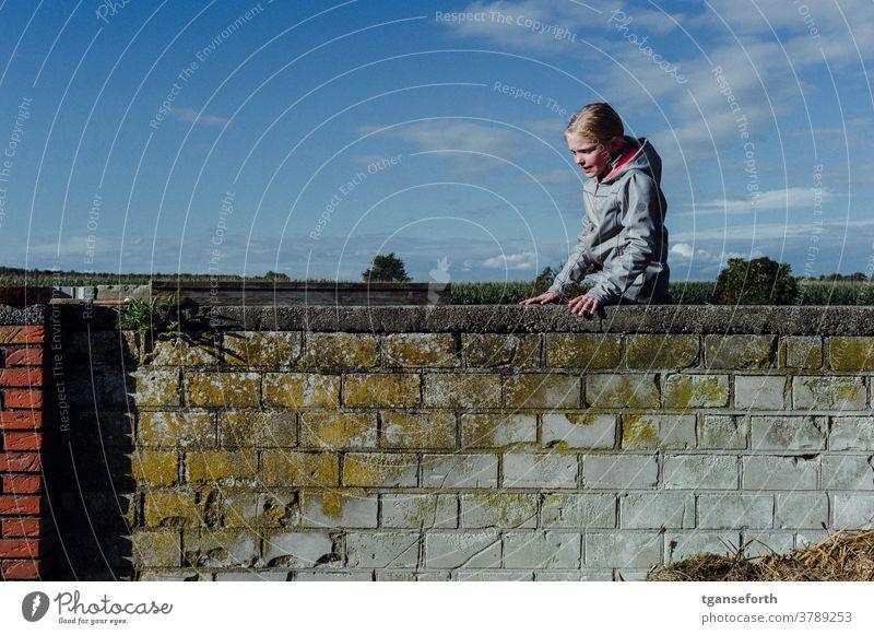 Auf der Mauer Kind Kindheit spielend spielerisch kletternd Mädchen Freude Außenaufnahme Farbfoto Mensch Spielen heiter Porträt mauerwerk Mauerstein alt