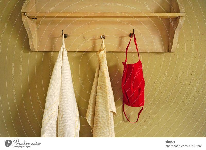 Eine rote Nasen- Mundschutzmaske hängt neben zwei alten, schmutzigen Handtüchern an einem der drei Haken einer Wandgarderobe aus Holz Handtuch Prävention Maske
