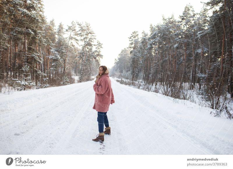 Junge hübsche stilvolle Frau, die sich im verschneiten Winterwald in Bewegung amüsiert. Mädchen Model Schnee Fröhlichkeit Lächeln Porträt stylisch Erwachsener