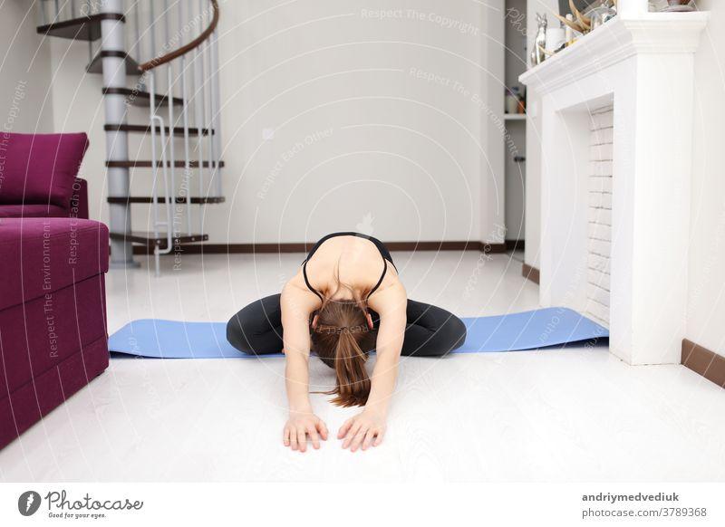 Macht Yoga-Übungen auf der Matte auf dem Boden. Junge Frau mit schlanker Körperform in Sportkleidung hat einen Fitness-Tag zu Hause im Haus. jung